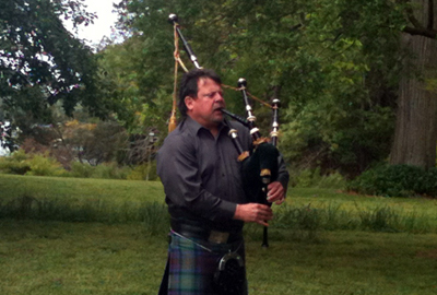 Tim Carey playing bagpipe at the garden