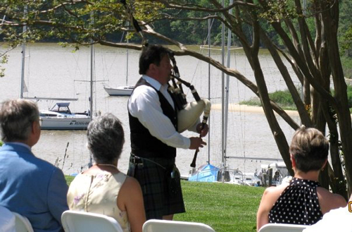 Tim Carey playing his bagpipe by a river at a wedding